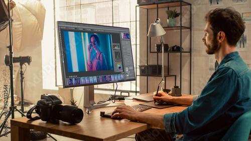 Professional Photographer Sitting at His Desk Uses Desktop Computer in a Photo Studio Retouches. After Photoshoot He Retouches Photographs of Beautiful Female Model in an Image Editing Software