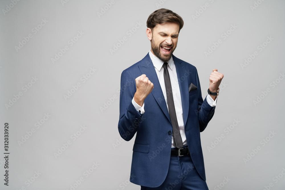 Fototapeta Very happy successful winner gesturing businessman over grey background