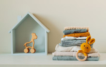 Organic Cotton Baby Clothes And Wooden Toys On The Shelf