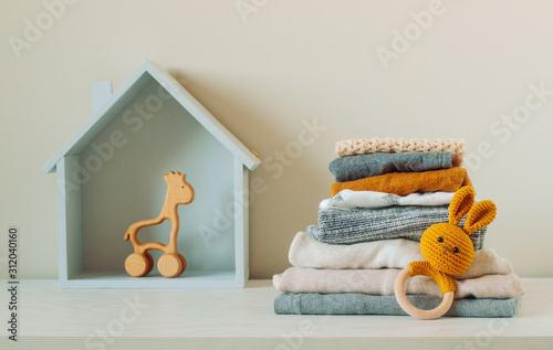 Photo Organic cotton baby clothes and wooden toys on the shelf