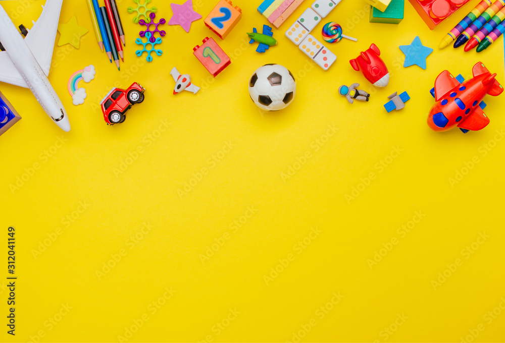 Fototapeta Frame of kids toys on yellow background with copy space