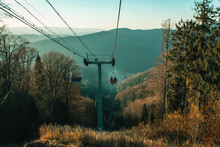 Ski Lift In The Mountains. Beautiful Sunny Landscape With Mountains. Blue Sky, Grass And Forest. Background Or Wallpaper.