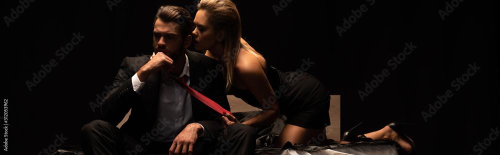 Fototapeta panoramic shot of beautiful elegant seductive couple sitting on bed in dark room