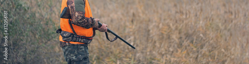 Photographie A man with a gun in his hands and an orange vest on a pheasant hunt in a wooded area in cloudy weather