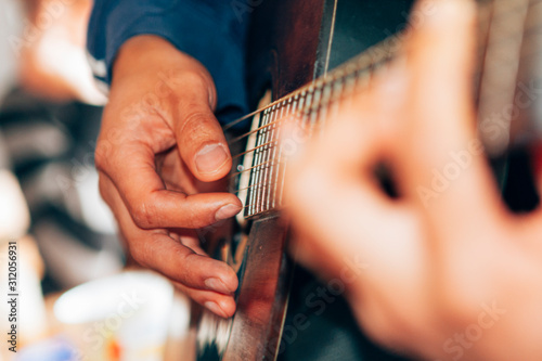 Fotografie, Tablou  close-up on male hands playing a classical guitar