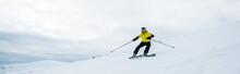 Panoramic Shot Of Sportsman Holding Ski Sticks While Skiing On White Snow