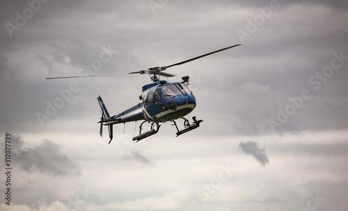 Fototapeta Blue helicopter in flight over gray sky