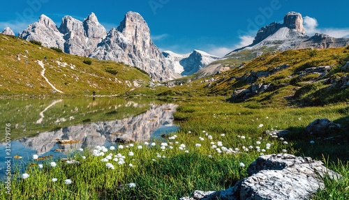 Wall mural - Awesome Alpine highlands in sunny day. Amazing Summer Landscape of Dolomites Alps. Wonderful Panoramic view  at Mountains Range and calm lake on foreground of Tre Cime di Lavaredo National park.