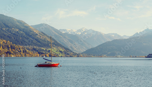 Wall mural -  Panoramic view of beautiful mountain landscape in Alps with Zeller Lake in Zell am See, Salzburger Land, Austria. Red yaht at calm water Wonderful Lake. under bright sunlight