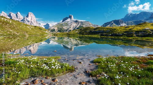 Wall mural - Amazing Nature Landscape. Alpine lake with crystal clear water and frash grass and flowers. Perfect Blue sky and mountains peaks. Incredible view of Dolomites Alps. Tre Cime di Lavaredo National park.