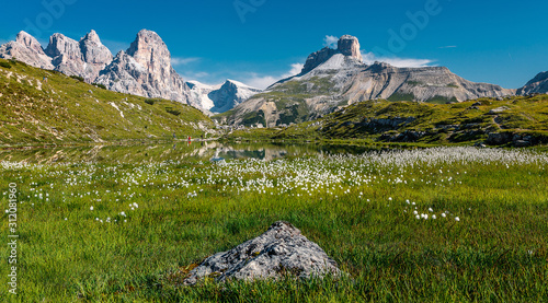 Wall mural - Colorful sunny morning view on calm lake, and mountains peaks . fairytale mountain valley of Tre Cime di Lavaredo National park under sunlit. Amazing Natural background. Impressive Wild area