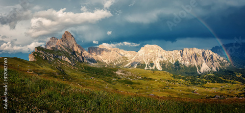 Wall mural - The rainbow over the seceda ridge, idyllic mountain scenery in the Dolomites Alps with Majestic Peaks, Overcast sky and Rainbow. Odle mountain range, Val Gardena in Dolomites. Italy. Amazing Nature