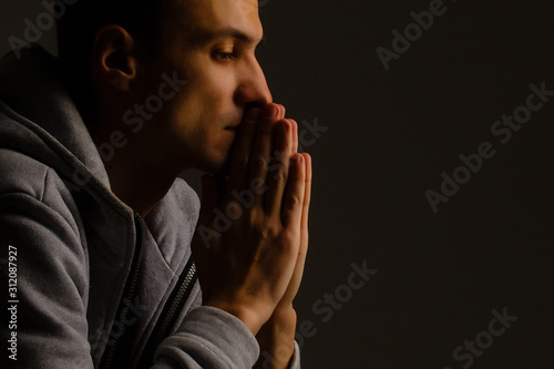 Leinwand Poster  Religious young man praying to God on dark background, black and white effect