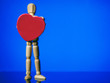 canvas print picture - Wooden male figure standing and holding red heart in his hands. Blue background, Copy space. Saint Valentine theme background.