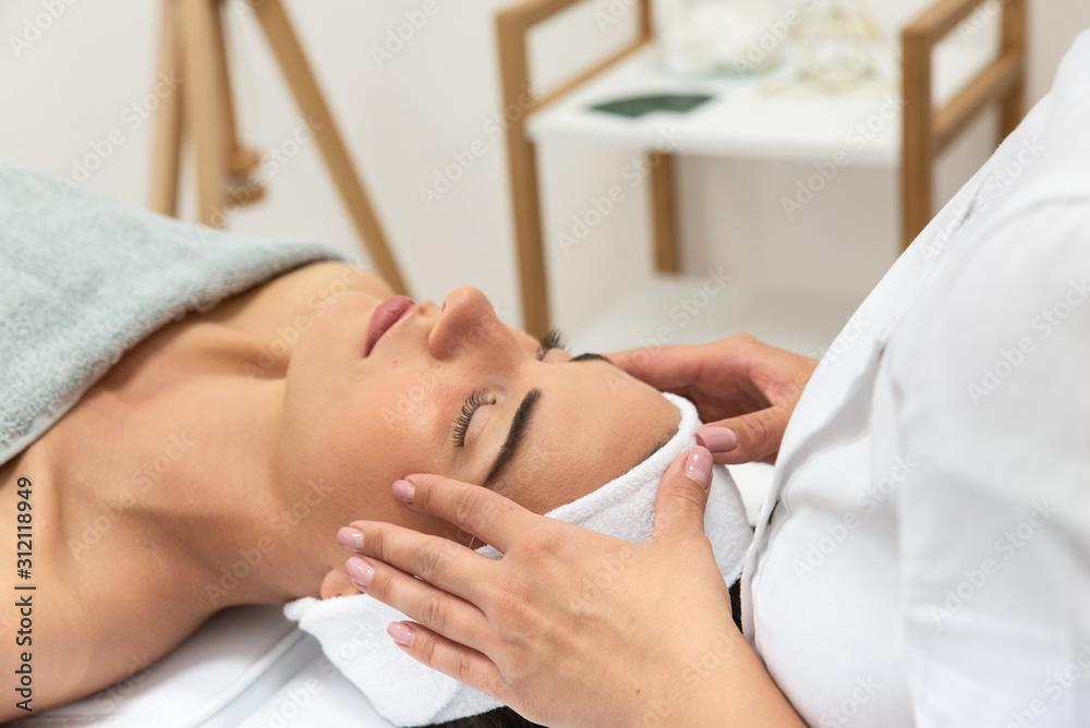 Fototapeta Kobieta leżąca z zamkniętymi oczami podczas zabiegu relaksacyjnego w salonie urody. Masaż twarzy.