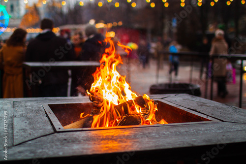 Logs burn with a bright flame in the city restaurant. Outdoors. Wallpaper Mural