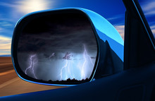 Life Is A Journey Concept. Difficulties Are Back. Rear View Mirror Car Showing Wheater Storm Backward And Sun Forward