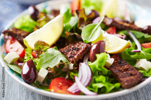 Foto Tasty salad with grilled beef steak, cherry tomatoes and lettuce