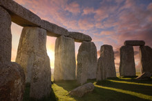 Inside The Stonehenge Circle Of Stones With A Sun Rays Filtering Through The ArchesDramatic Sky Sunrise Behind It