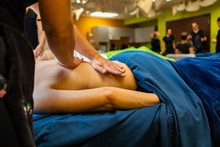 A Closeup Shot Of A Pupil Practicing Sliding And Gliding Hand Techniques In A Swedish Massage Classroom, With Blurry Pupils Behind And Copy Space