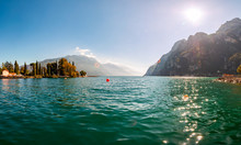 Panoramic View Against Bright Sun Rays Above The Rocks On Beautiful Garda Lake Shore In Riva Del Garda City Surrounded By High Dolomite Mountains