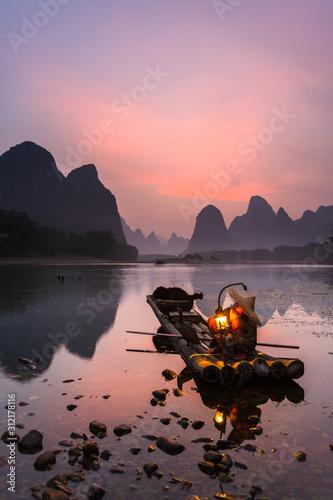 Fotografie, Tablou Cormorant fisherman on the Li River, near the town of Xingping in Guangxi province, China