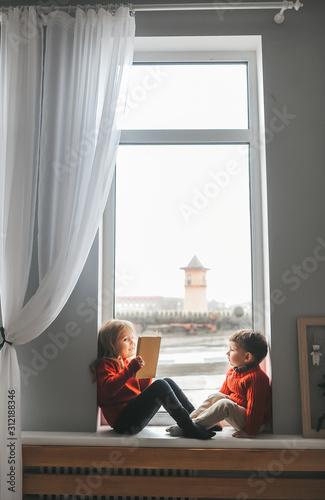 Fotografie, Tablou  Boy and his sister home playing on the window sill and  reading books