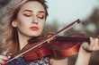 face of a beautiful girl with a violin under her chin outdoors, young woman playing a musical instrument on nature in solitude, concept music and feelings