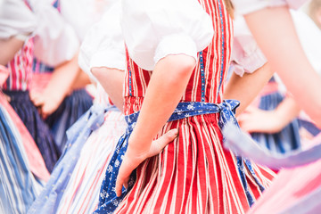 Closeup of hands in waists of many dancing school girls. Young women in period costumes perform folklore dances in Cesky Krumlov (UNESCO site in Czech Republic) to welcome spring and Easter Holiday