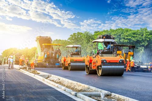 Construction site is laying new asphalt road pavement,road construction workers and road construction machinery scene. - fototapety na wymiar