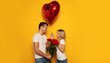 Happy Valentine's Day. Close-up photo of a lovely couple in casual clothes, who are celebrating Valentine's Day and holding a bouquet of red roses and a big heart-shaped balloon in their hands.