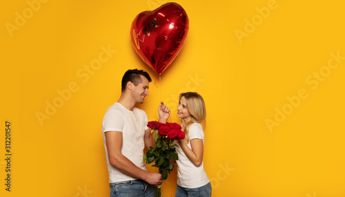 Obraz Happy Valentine's Day. Close-up photo of a lovely couple in casual clothes, who are celebrating Valentine's Day and holding a bouquet of red roses and a big heart-shaped balloon in their hands. - fototapety do salonu