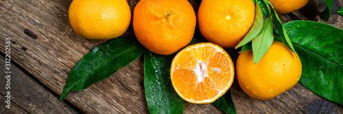 Fototapeta Mandarynki  mandarynka-mandarynki-klementynka-pomaranczowe-owoce-z-zielonymi-liscmi-na-drewnianym-stole-swiezy