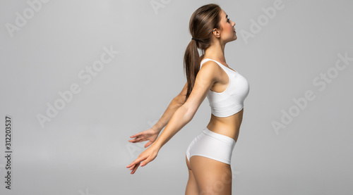 Slim tanned woman in white lingerie with perfect body isolated over gray background