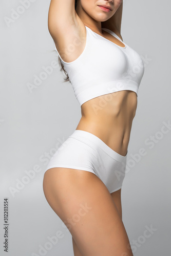 Close up shot of unrecognizable fit woman in lingerie isolated on white background Fototapeta