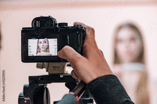 Obraz Selective focus of videographer working with attractive model in photo studio - fototapety do salonu