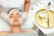 Kosmetolog pielęgnuje twarz młodej kobiety. Pięlęgnacja twarzy.