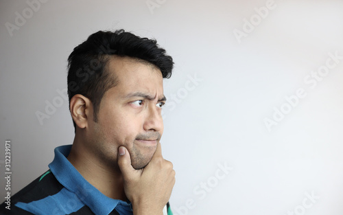 Fotomural right side face of an asian man with inquisitive expression looking towards a copy space with white background
