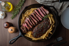 Sirloin Steak With French Fries In Iron Skillet Pan