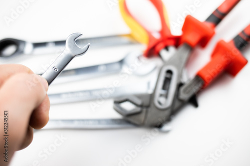 Obraz klucz płaski trzymany w dłoni, w tle zestaw narzędzi - fototapety do salonu