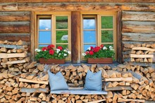 Rural Wooden House Windows With Flowers And Wooden Bench, Dolomites Italy, European Alps