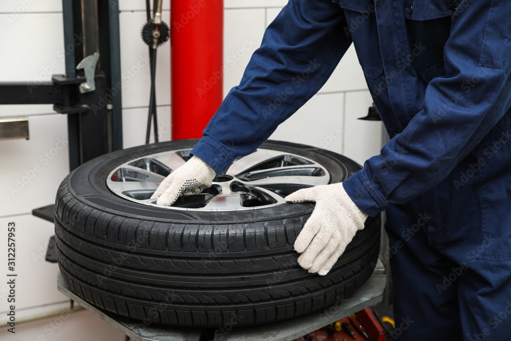 Fototapeta Man working with tire fitting machine at car service, closeup