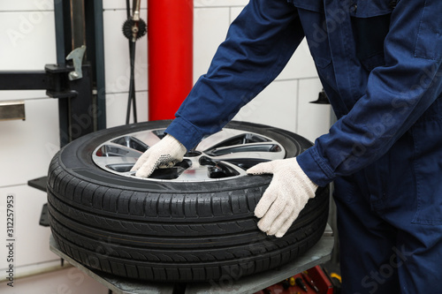 obraz PCV Man working with tire fitting machine at car service, closeup