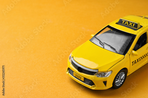 Yellow taxi car model on orange background. Space for text Fototapete