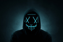 Portrait Of An Anonymous Man, Hacker Wearing Neon Mask Over Dark Background