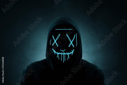 Fotografía Portrait of an anonymous man, hacker wearing neon mask over dark background