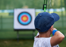 Young Boy Aims At A Target With His Bows And Arrows