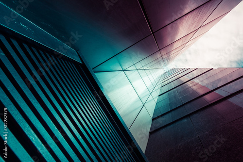 Abstract background. View through modern high rising skyscraper chimney upwards to blue sky with white clouds - abstract architecture detail background in turquoise teal blue to burgundy purple colors