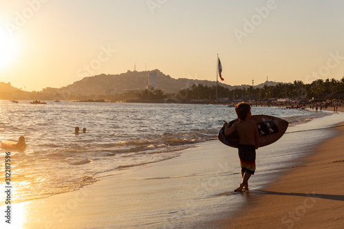 Fotografie, Tablou  Niño aprendiendo a surfear en playas de Acapulco