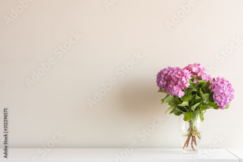 Fotografering Pink hydrangea flowers with green leaves in glass vase on white side board again